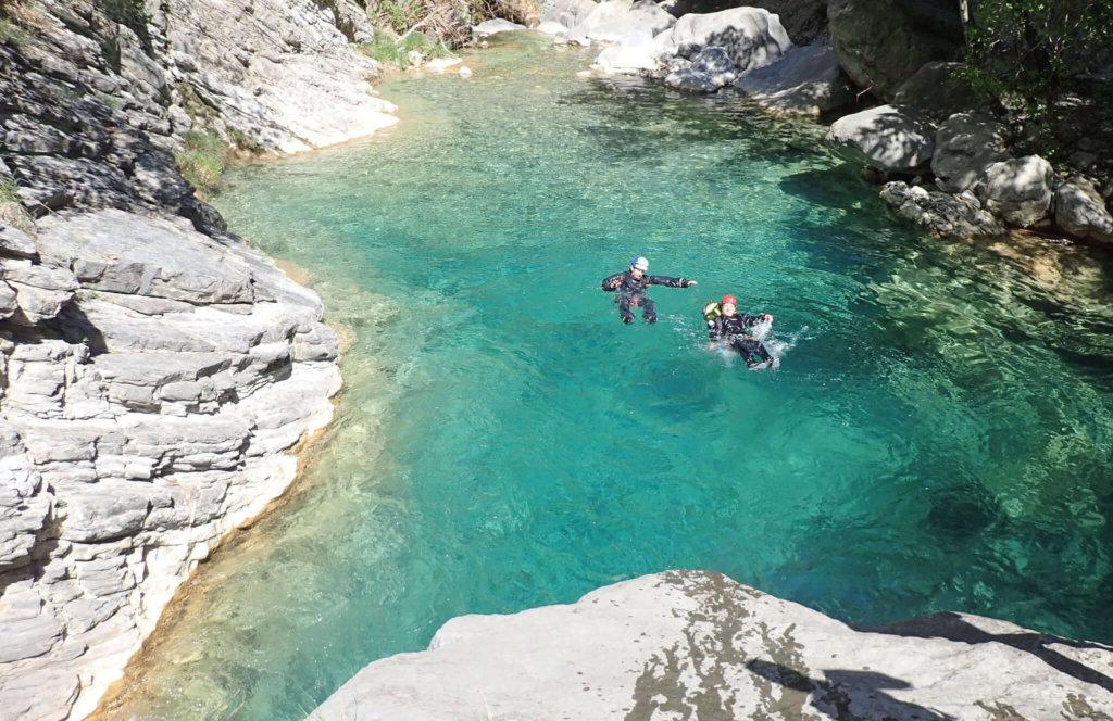 Des pratiquants de canyoning en France flottent dans une eau limpide.