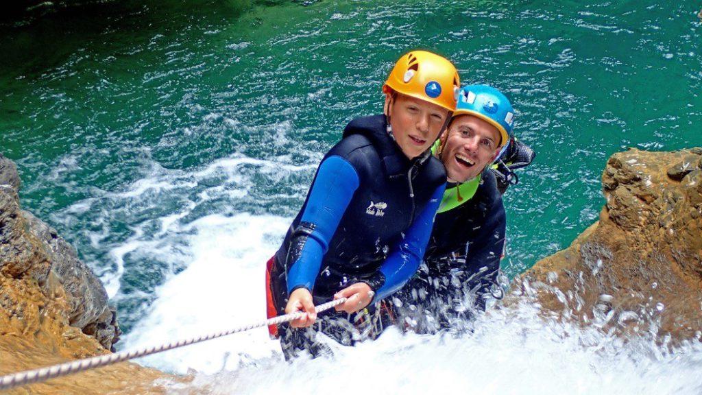 Deux personnes descendent en rappel un toboggan de canyoning.