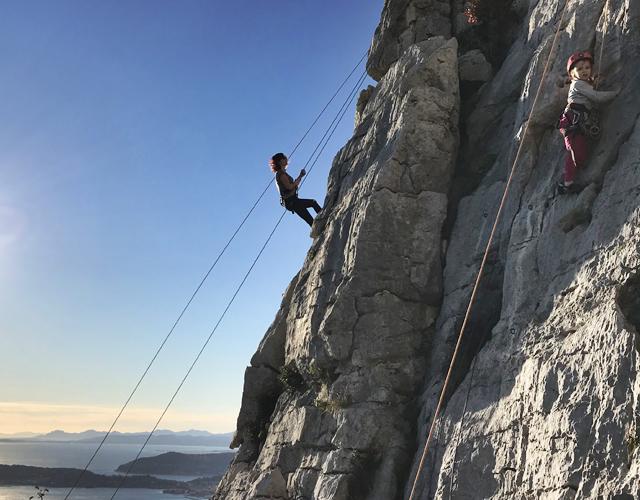 Photographie d'un adulte et d'un enfant en train d'apprendre l'escalade.