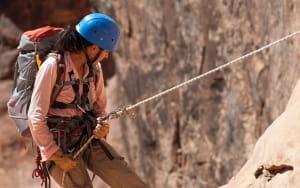 Jeune femme pratiquant canyoning et escalade.