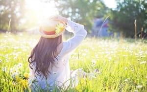 Femme assise dans l'herbe face au soleil