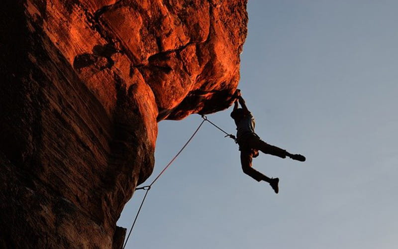 Homme qui pratique l'escalade en montagne